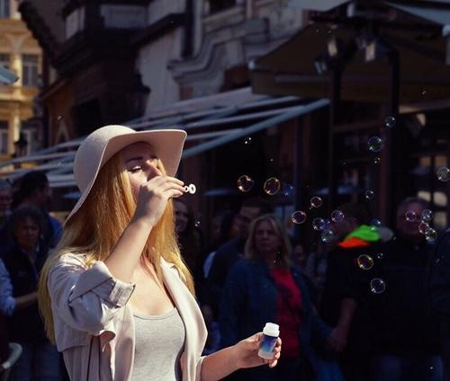 Chica lanzando burbujas en un mercado