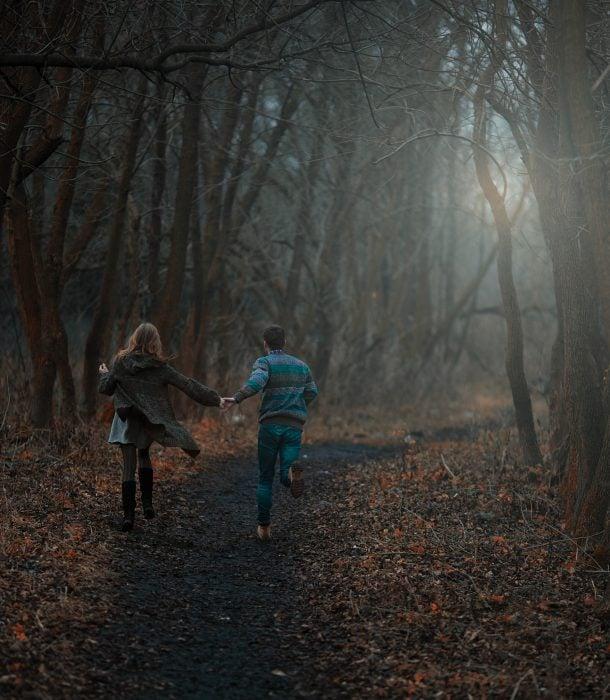 Pareja de novios corriendo tomados de las manos entre un bosque