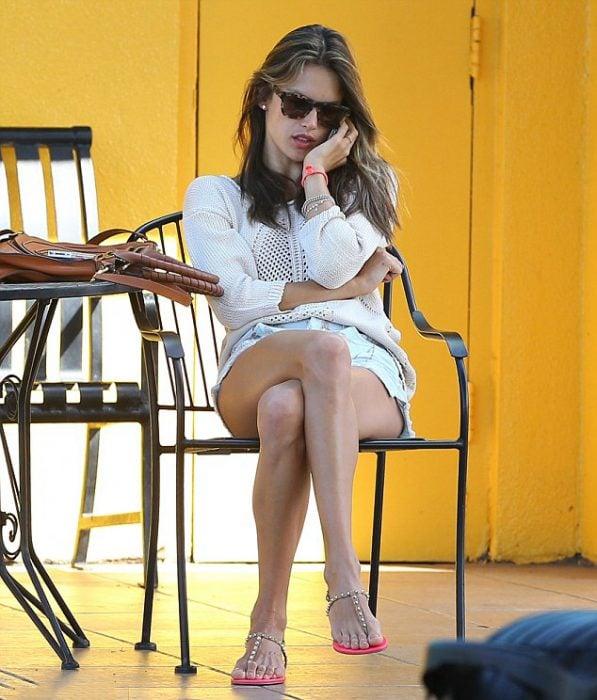 Chica sentada en una cafetería con los pies cruzados