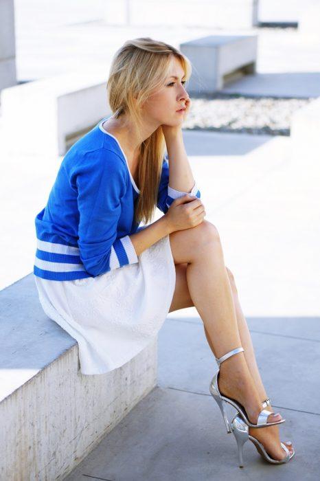 Chica sentada en unas escaleras con las piernas cruzadas