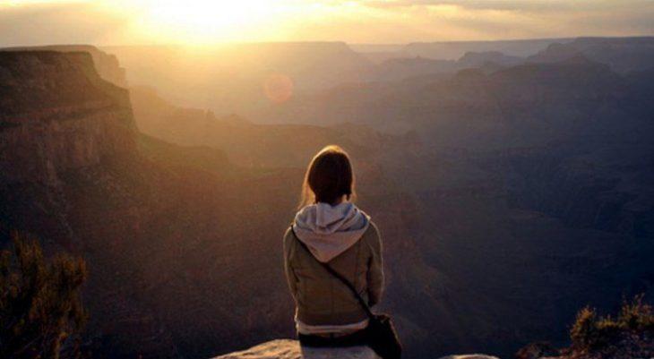 chica observando el horizonte en la montaña