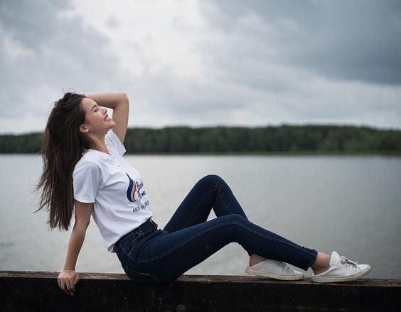 Chica sonriente con cabello largo y oscuro posa sentada con las pierna extendidas mientras mira hacia arriba y pone su mano en la cabeza