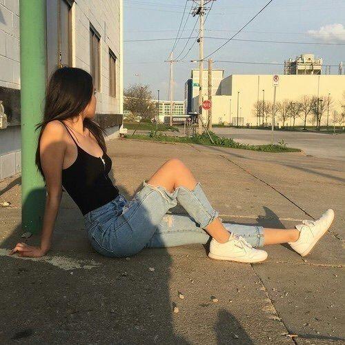 Chica delgada con blusa de tirantes negra y pantalón mezclilla posa sentada en el piso mientras se recarga en una poste verde