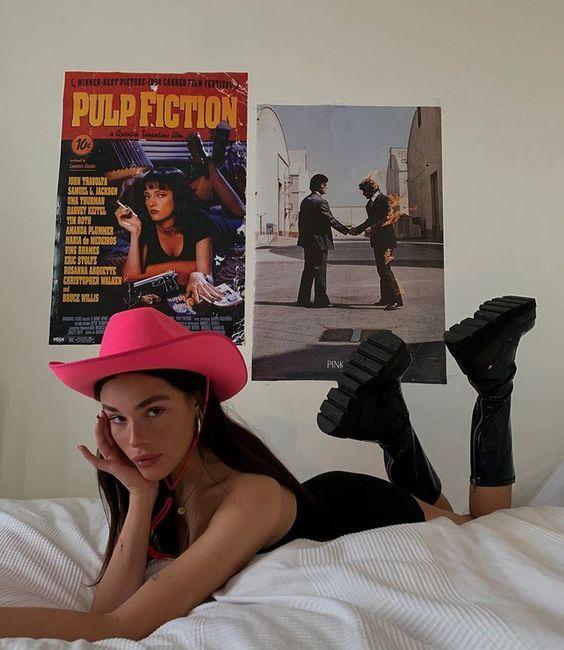Chica muy delgada de cabello largo y lacio posa boca abajo mientras viste un vestido negro corto de tirante con una botas de hule negras largas y un sombrero rosa neón