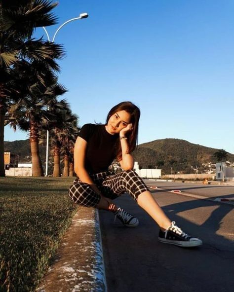 Chica delgada de cabello oscuro lacio vistiendo pantalón a cuadros negro con blusa negra posa sentada recargando su brazo en la rodilla izquierda