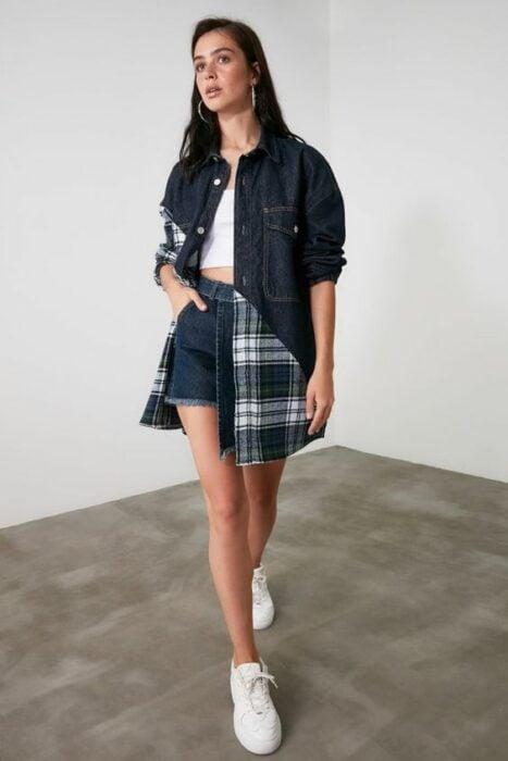 Chica de cabello largo posando de pie con una chaqueta de mezclilla y una mano dentro del bolsillo izquierdo del short