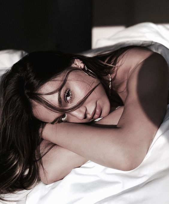 Chica morena con cabello largo y lacio posa boca abajo en una cama con cobijas blancas
