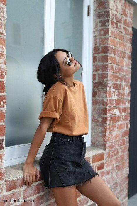 Chica morena con cabello recogido en un chongo bajo posa recargando sus manos en una ventana trasera mientras viste falda negra, blusa naranja y lentes de sol