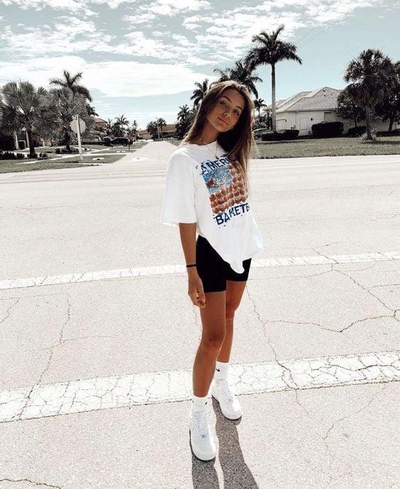 Chica rubia bronceada de cabello castaño suelto con biker shorts, tenia blancos y blusa amplia blanca
