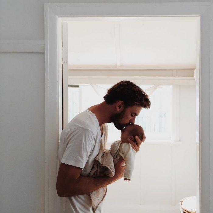 Hombre cargando y besando en la frente a una bebé