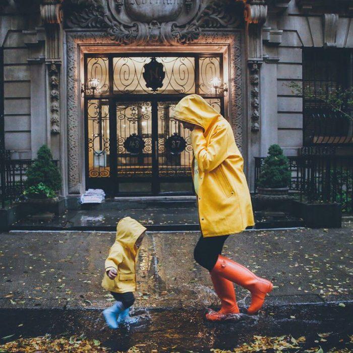 Madre e hija jugando bajo la lluvia