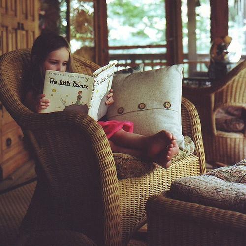 Niña leyendo un libro sentada en un sofá