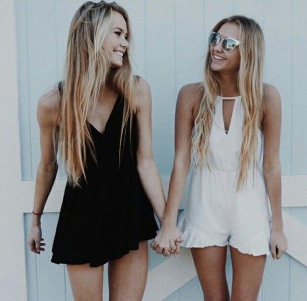 Chicas tomadas de las manos sonriendo