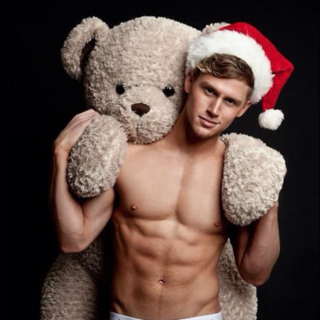 Chico vestido de santa cargando un oso de felpa