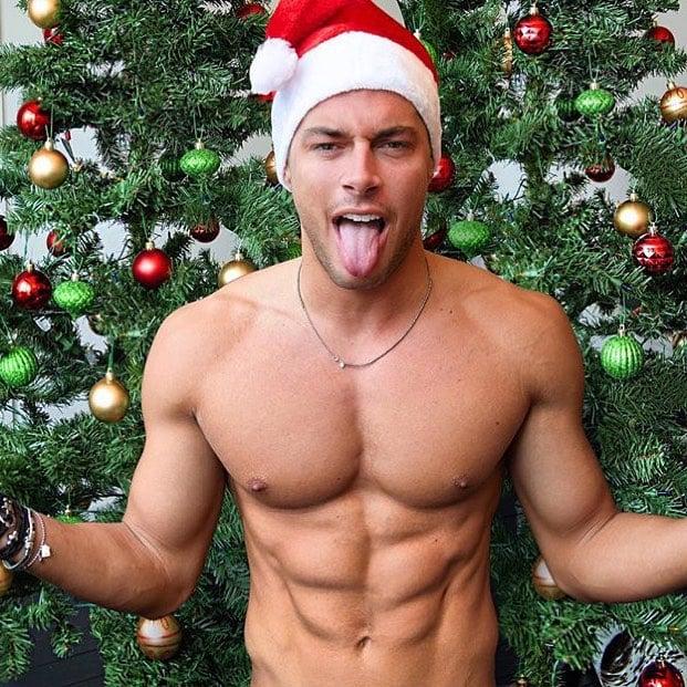 Chico vestido de santa parado frente al árbol de navidad