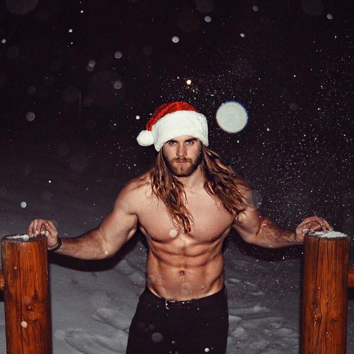 Brock O'Hurn sin camisa y usando un gorro de navidad