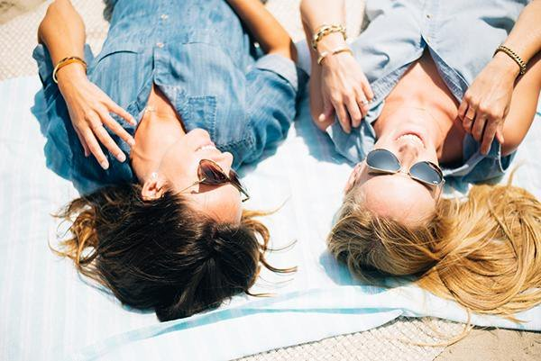 Chicas recostadas bajo el sol sin hablar
