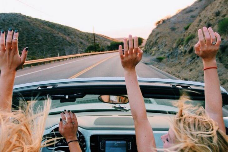 Chicas en un auto convertible en la carretera