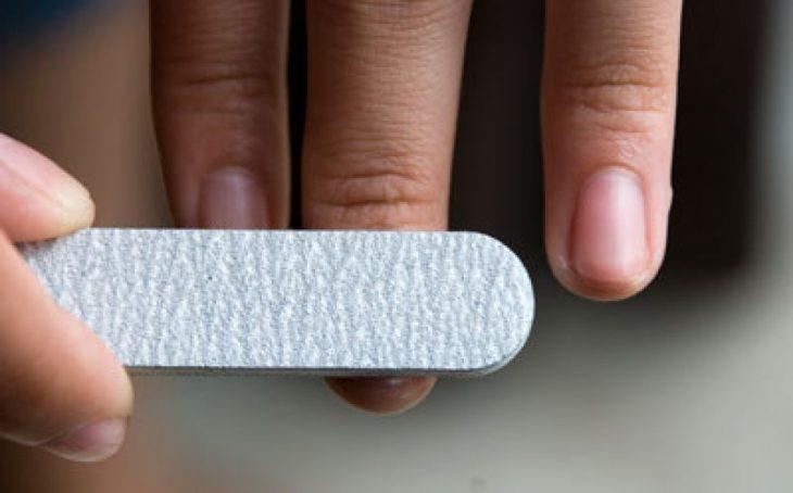 Chica puliendo sus uñas con una lima