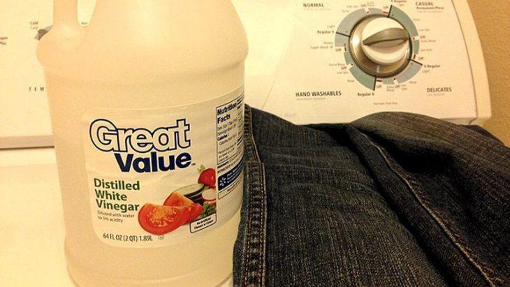 vinagre y pantalón sobre una lavadora
