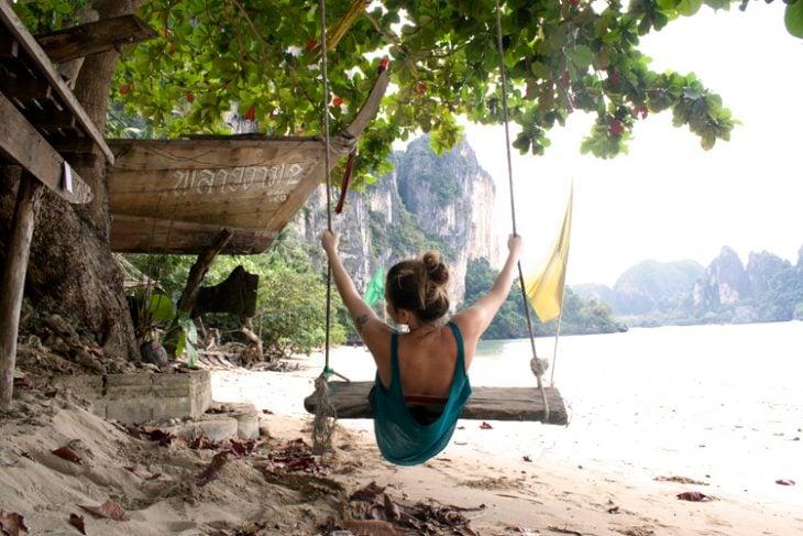 mujer en un columpio en la playa