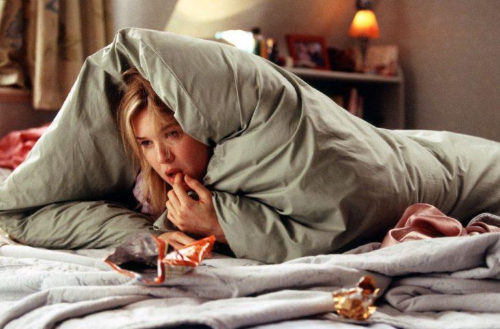 Escena de la película el diario de Bridget Jones chica recostada en la cama comiendo papas