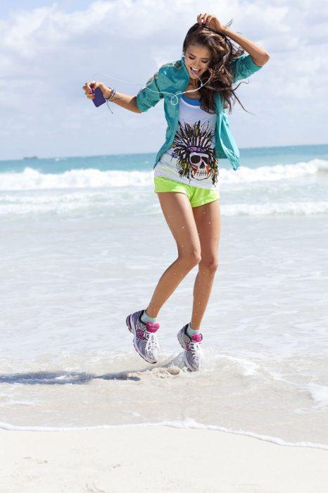 Chica escuchando musica y saltando en la arena del mar