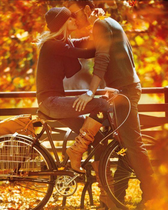 Pareja de novios besándose mientras ella está sentada en una bicicleta