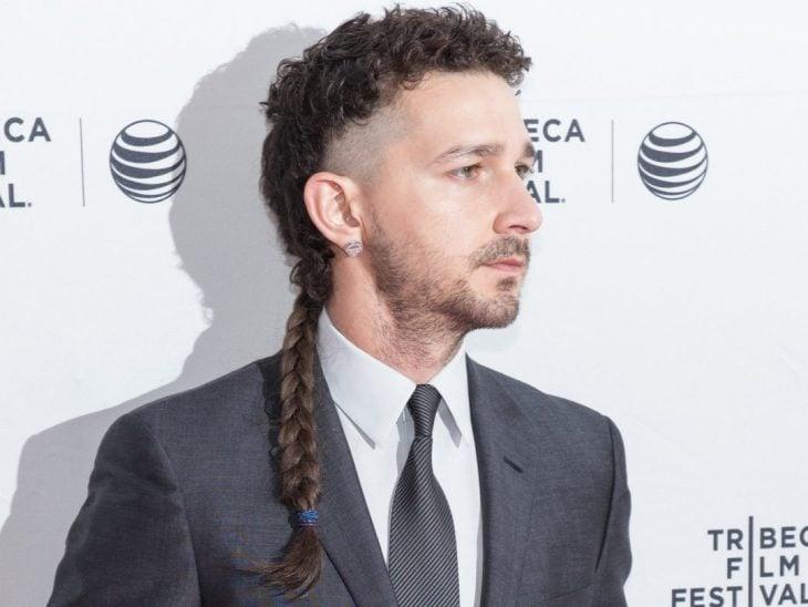 hombre con cabello corto a los lados y trenza larga atrás