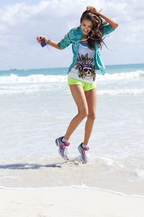 Chica escuchando música en la playa