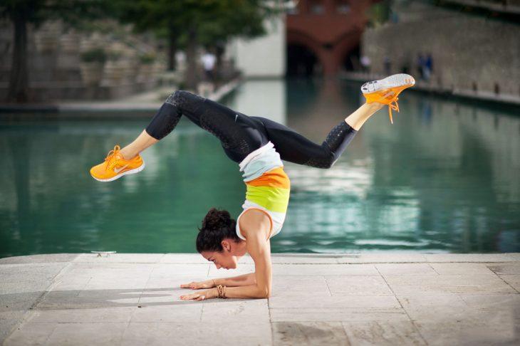 Chica practicando yoga frente a un a alberca