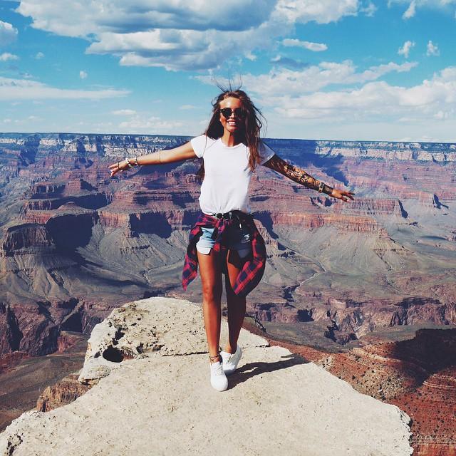 Chica parada en una montaña con los brazos abiertos