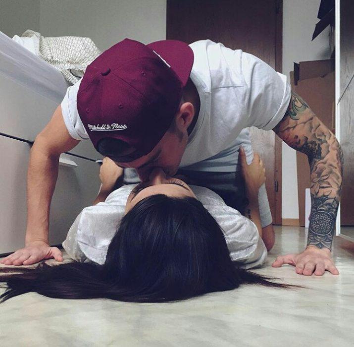 pareja en el suelo dándose un beso