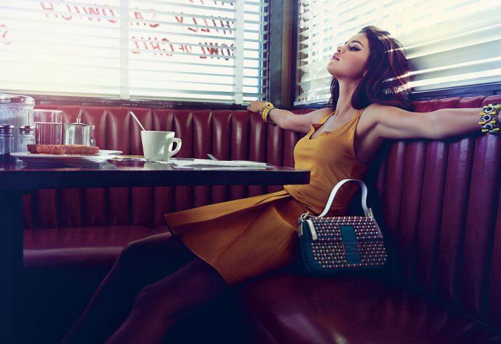 mujer sentada en restaurante brazos abiertos