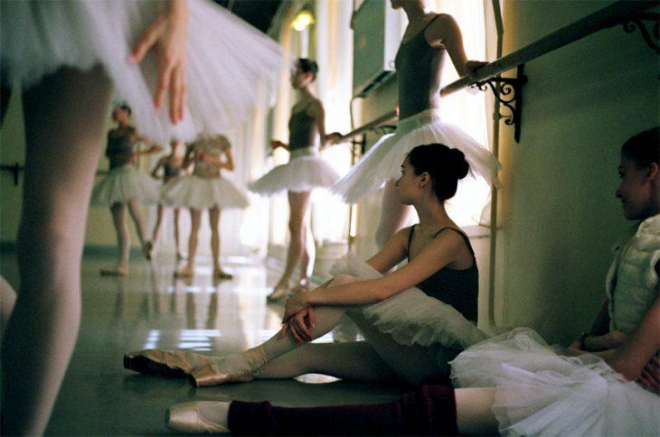 Bailarina de ballet sentada en el suelo mientras ve a otras bailar