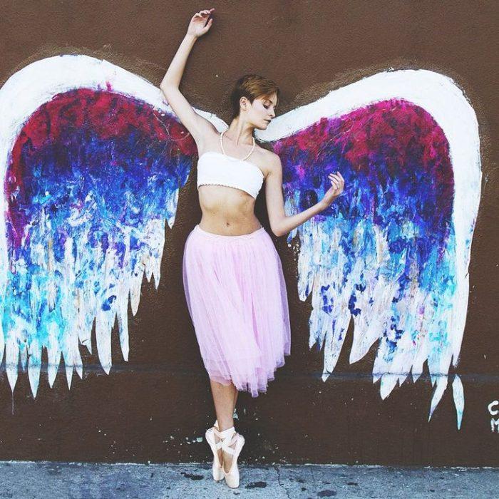 Bailarina de ballet recargada sobre una pared en la que tiene unas alas pintadas
