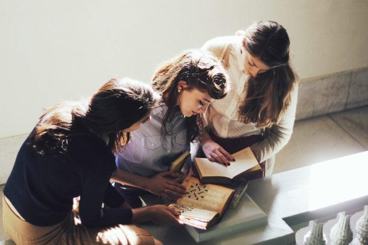 Chica junto a otras dos mientras están viendo un libro