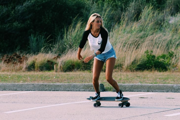 Chica en una patineta haciendo piruetas