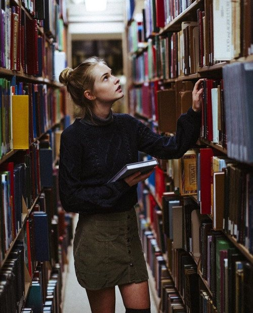 Chica en una biblioteca eligiendo libros