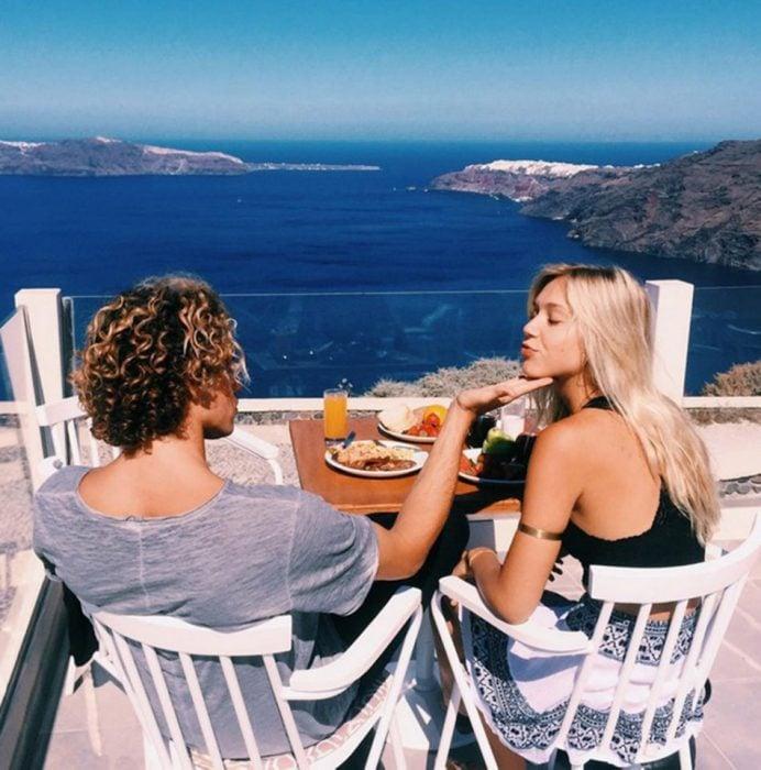 pareja en balcon comiendo vista al mar