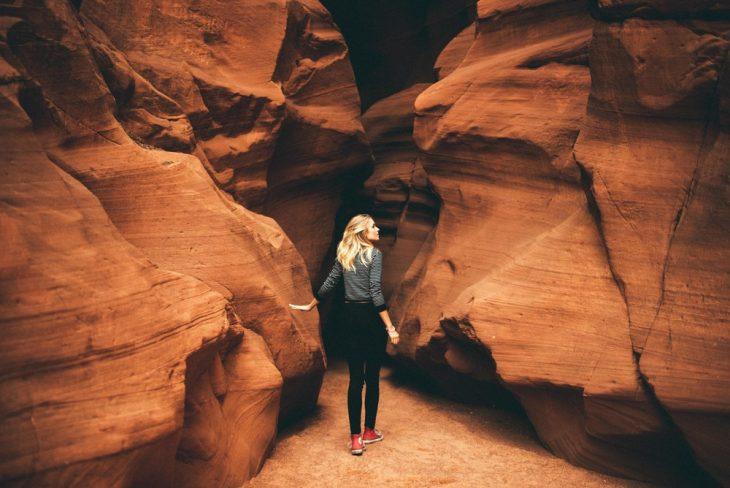 Chica intentando atravesar por enmedio de unas rocas