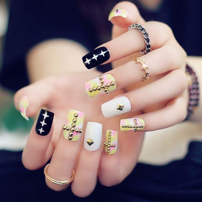 Chica con las uñas en color negro, blanco y amarillo