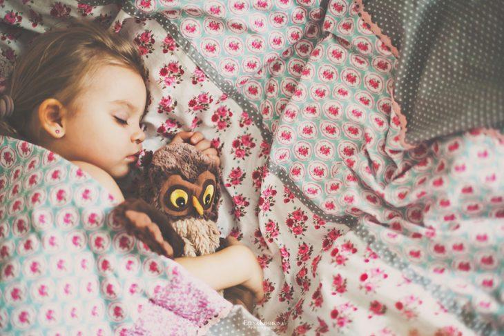 niña dormida abrazando peluche buho