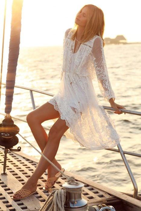Mujer recargada sobre la borda de un barco tomando el sol