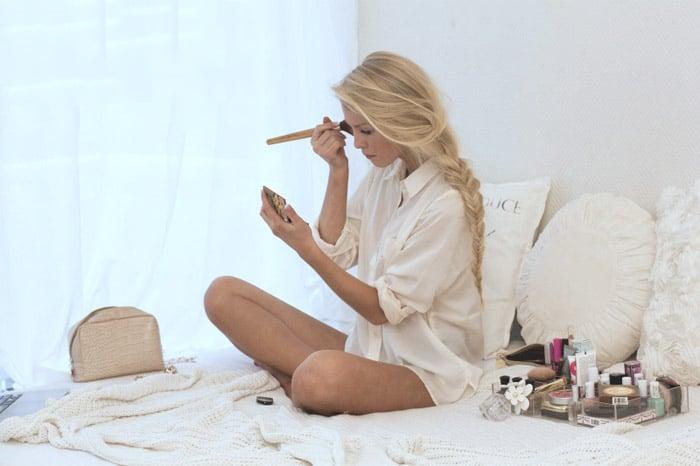 Chica sentada en una cama maquillándose