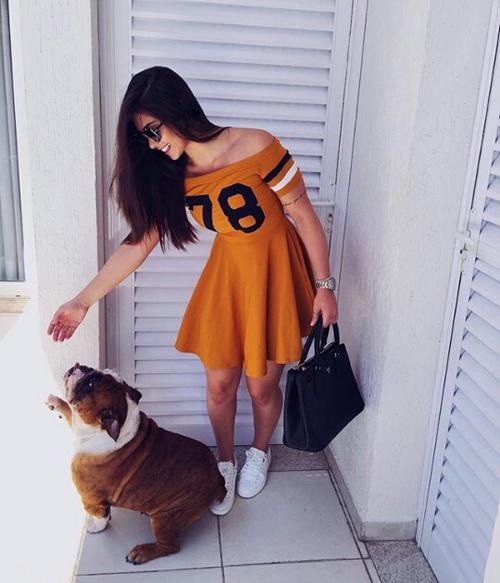 Chica dandole de comer a un perro que está fuera de su casa