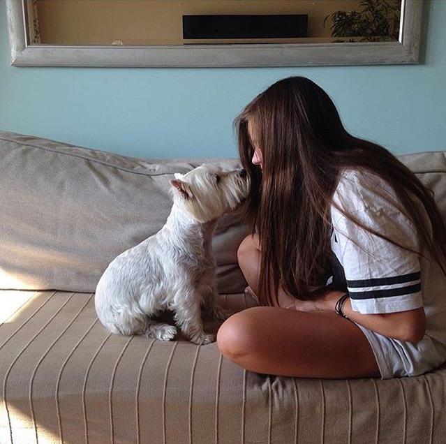Chica sentada en un sofá junto a su perro