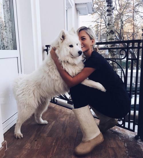 Chica abrazando a un perro en la entrada de su casa