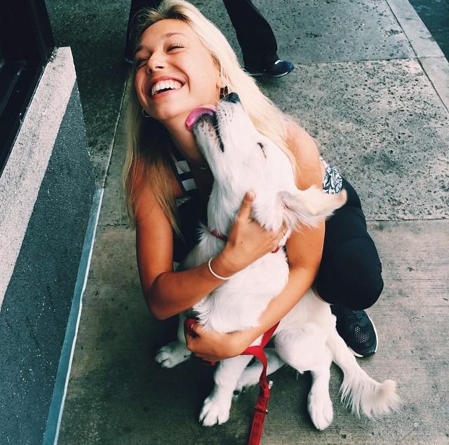 Chica junto a un perro que le está dando una lamida