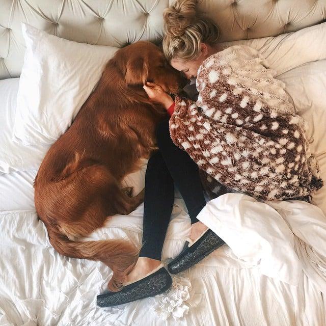 Chica recostada en una cama junto a su perro